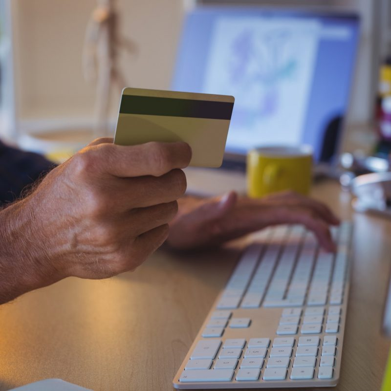 Cropped businessman shopping online with credit card at office